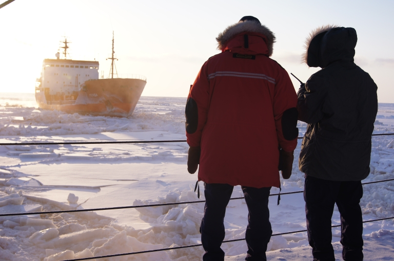 <p>Crew members of the US Coast Guard Cutter Healy observe the Russian tanker vessel Renda as it follows their trail through the ice toward Nome, Alaska January 8, 2012 in the Bearing Sea.</p>