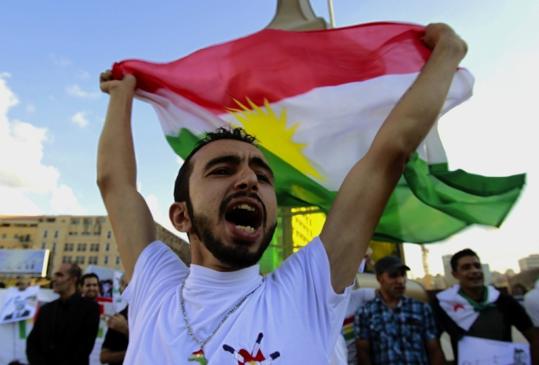 <p>A Syrian Kurd residing in Lebanon holds up a Kurdish flag during a protest in Beirut on Oct. 7, 2012 to mark the first anniversary of the assassination of the Syrian Kurdish opposition leader, Meshaal Tamo.</p>