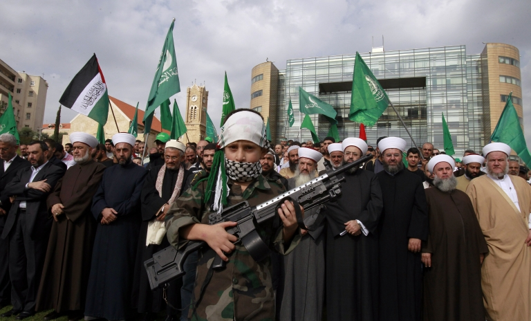 <p>A Palestinian boy carries a toy gun during a rally by Sunni Muslim group Jamaa Islamiya against the ongoing Israeli occupation of Gaza outside the offices of the United Nations Economic and Social Commission for Western Asia (ESCWA) in the Lebanese capital of Beirut in November 2012.</p>