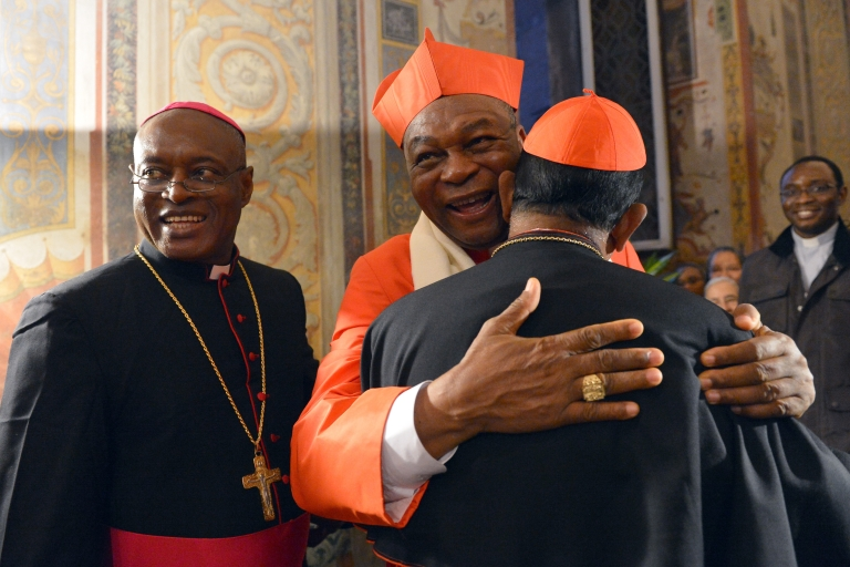 <p>Nigerian cardinal John Onaiyekan (C) greets visitors druing the courtesy visit after being appointed by the pontif on November 24, 2012 at the Apostolico Palace at the Vatican. Six non-European prelates are set to join the Catholic Church's College of Cardinals, a move welcomed by critics concerned that the body which will elect the future pope is too Eurocentric.</p>