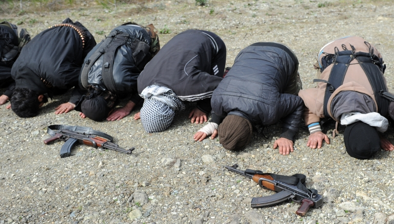 <p>Rebel fighters offer prayers near their position as they prepare to fight against pro-Syrian regime forces on the Jabal al-Turkman mountains in Syria's northern Latakia province, on February 5, 2013.</p>
