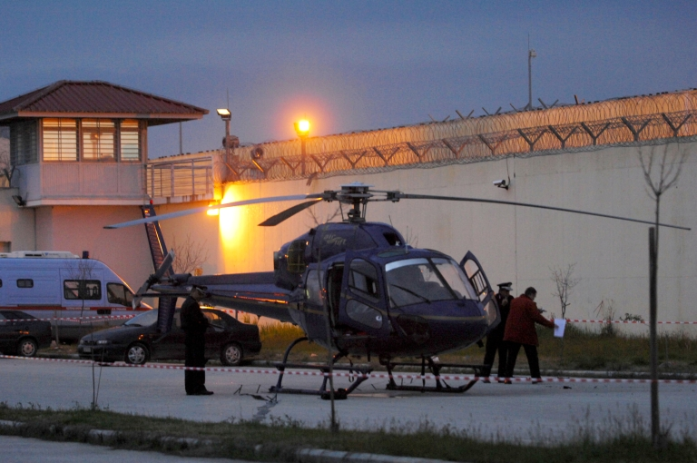 <p>This picture taken on February 24, 2013 shows police investigating by a helicopter in the northern Greece Trikala prison's yard. A helicopter swooped down on a prison courtyard on February 24 as armed men on board fired on guards and lowered a rope to help a convicted killer make his fourth attempt to escape from a Greek prison. But the plot was foiled after the prisoner was shot and the chopper forced to land in the prison's parking lot.</p>