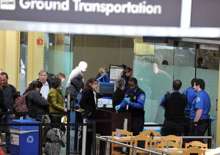 <p>Transportation Security Administration (TSA) personnel work at the Ronald Reagan National Airport in Washington, DC, on March 4, 2013.</p>