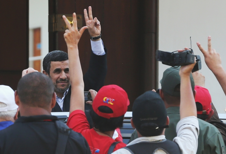 <p>Iranian President Mahmoud Ahmadinejad (L) waves to the crowd while departing from the funeral for Venezuelan President Hugo Chavez at the Military Academy on March 8, 2013 in Caracas, Venezuela.</p>