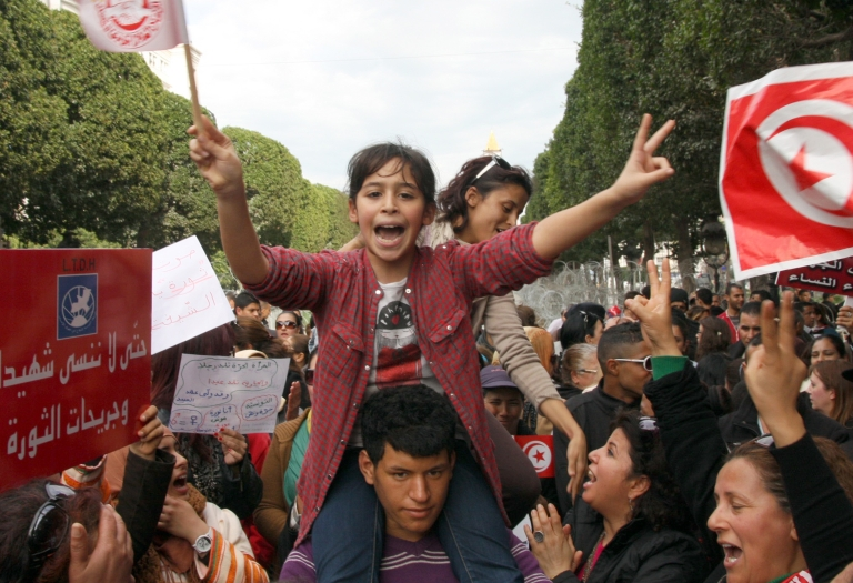 <p>A Tunisian young girl flashes the sign of victory shooting slogans during a demonstration on March 9, 2013 in Tunis.</p>