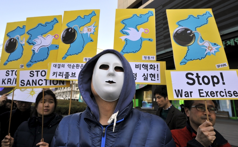 <p>Anti-war activists wearing masks hold placards showing the Korean Peninsula during a protest against a joint military exercise between South Korea and the US, called Key Resolve, near the US embassy in Seoul on March 11, 2013.</p>