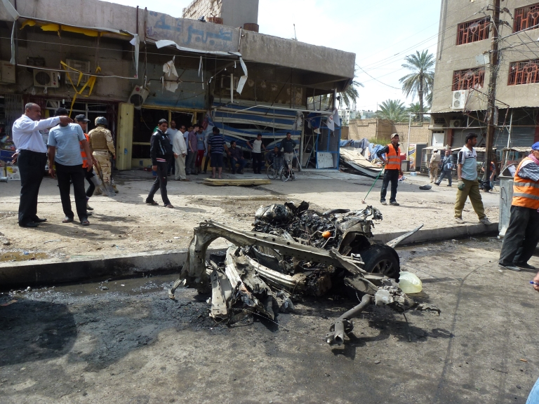 <p>People look at the remains of a car bomb explosion near the fortified 'Green Zone' in the capital of Baghdad, on March 19, 2013. A wave of attacks and explosions in Iraq killed more than 50 people and officials delayed provincial polls, highlighting security concerns on the eve of the 10th anniversary of the US-led invasion.</p>
