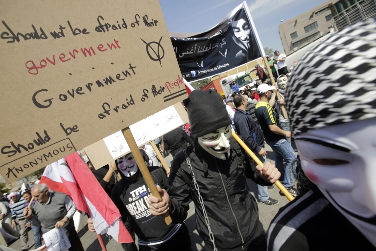<p>Lebanese protesters wearing a Guy Fawkes mask used by the Anonymous movement carry placards during a protest organized by the public sector employees on March 21, 2013 near the Presidential Palace in Baabda east of the Lebanese capital Beirut, to demand an increase in wages.</p>