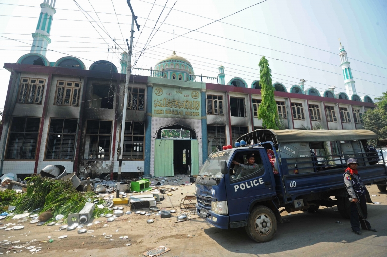 <p>Policemen stand guard outside a partially-burnt mosque in Meiktila, central Myanmar on March 22, 2013. The country has suffered religiously motivated riots and attacks for many months.</p>