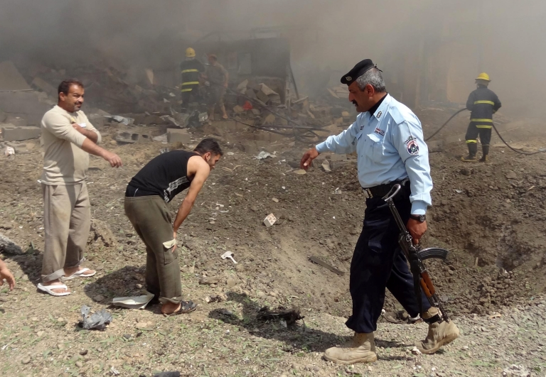 <p>Iraqis look at a crater near a policeman at the site of a car bomb that detonated near a Shiite mosque killing three people and injuring 70 others on March 29, 2013 in Kirkuk.</p>