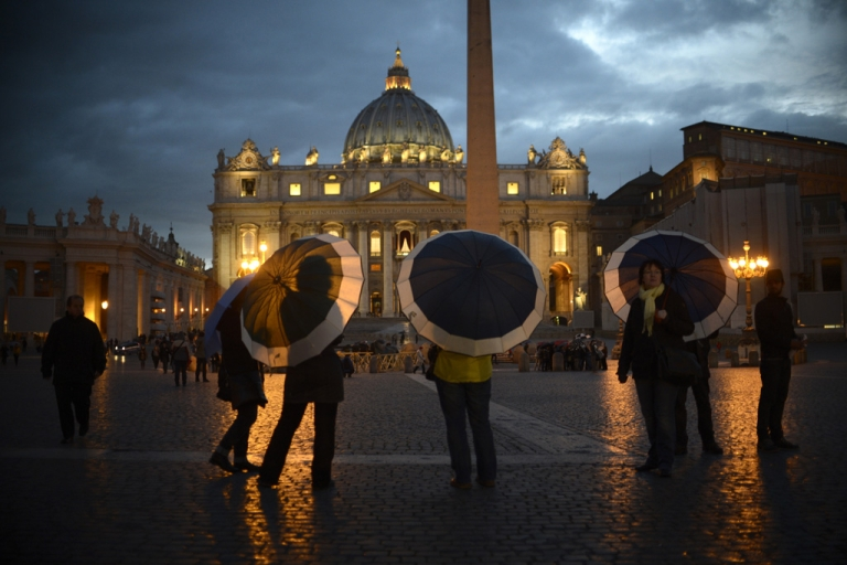 <p>Tourists hold umbrellas as they stand on St Peter's square on March 11, 2013 at the Vatican.</p>