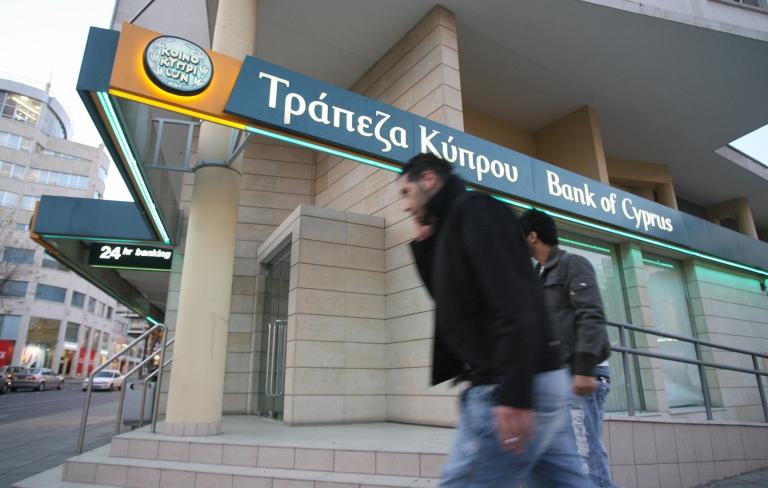 <p>Nicosia, CYPRUS: Two men walk past a Bank of Cyprus branch on Nicosia's Makarios main thoroughfare.</p>
