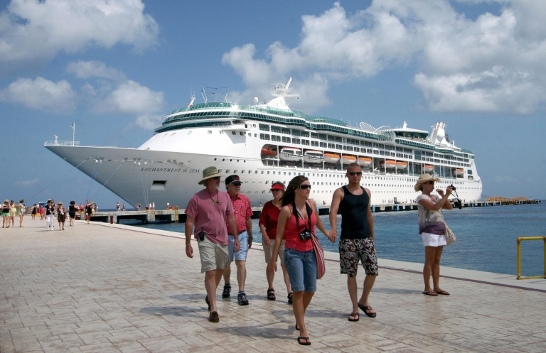 <p>Tourists walk at Cozumel's port, Mexico, after arriving on board of the 'Enchantment of the Seas' cruise ship, on May 27, 2009.</p>