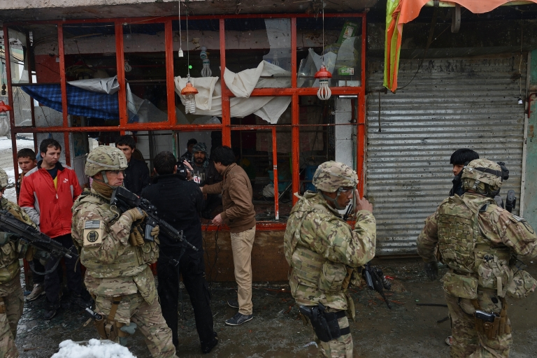 <p>US soldiers at the scene of a suicide attack against a bus carrying Afghan army personnel in Kabul in February 2013.</p>