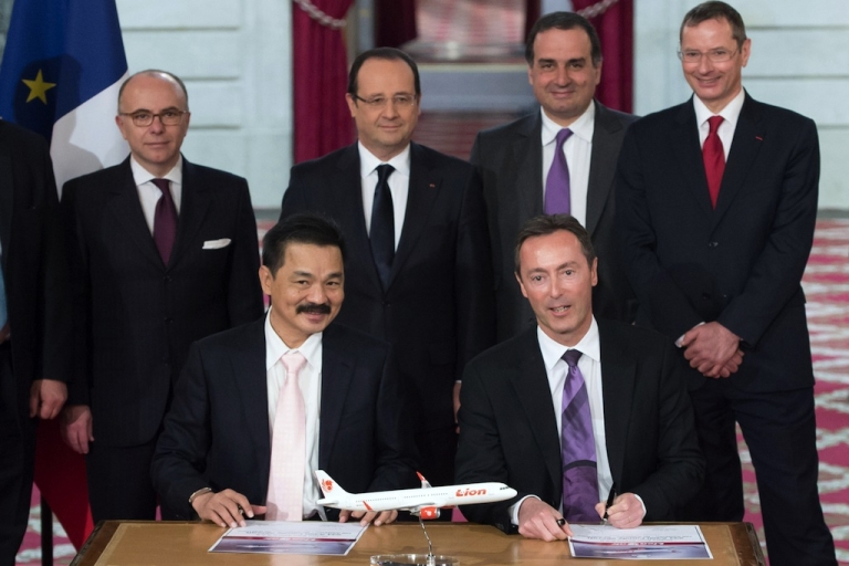 <p>Lion Air founder and president director Rusdi Kirana (L) and French CEO of European aerospace giant Airbus Fabrice Bregier (R) pose with France's President Francois Hollande (C, background), after signing a contract during a ceremony at the Elysee presidential palace in Paris March 18, 2013.</p>