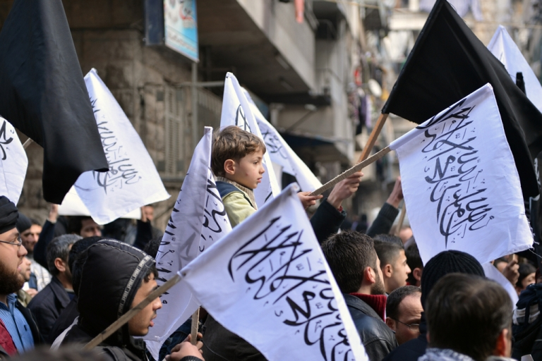 <p>Syrian supporters of the Jabhat al-Nusra group wave flags as they march during an anti-regime demonstration in Aleppo on Feb. 8, 2013.</p>