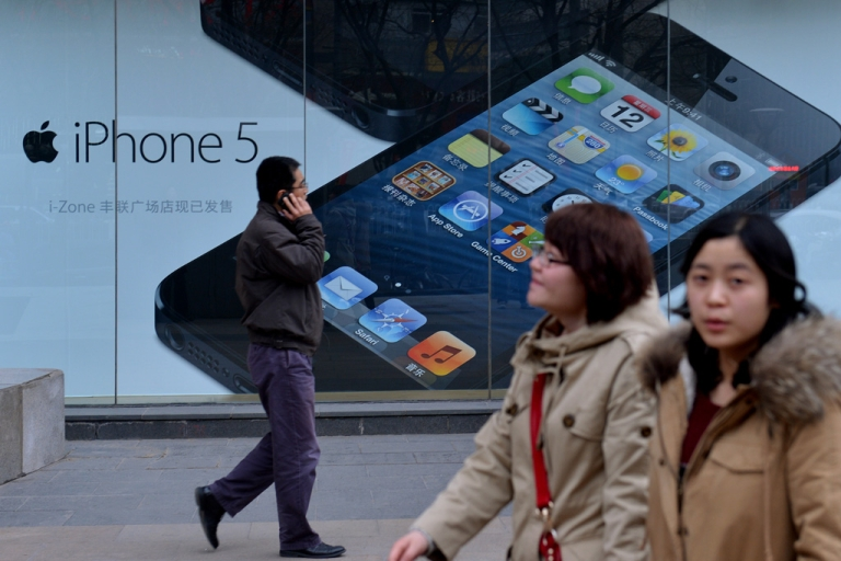 <p>Shoppers walk past an Apple reseller in Beijing on March 18, 2013. Apple was recently targeted over its consumer-service practices in China during a state television broadcast focusing on consumer rights, allegedly claiming the US company treated its Chinese customers differently when it came to service and warranties.</p>