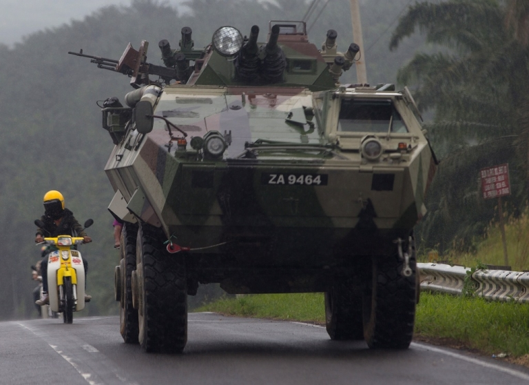 <p>Malaysian soldiers in an armored personnel carrier (R) travel in a convoy in Felda Sahabat on March 6, 2013.</p>