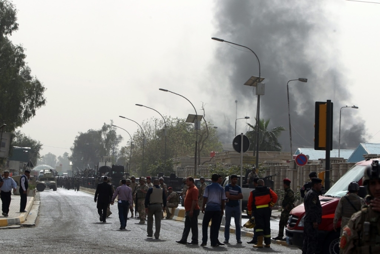 <p>Smoke billows from the scene of a car bomb attack in Baghdad, on March 14, 2013. A coordinated string of bombings and brazen assault on a ministry near Baghdad's heavily fortified Green Zone killed 18 people, in the Iraqi capital's deadliest violence this month.</p>