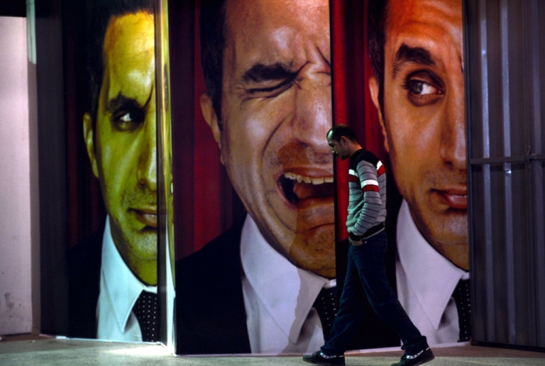 <p>An Egyptian walks past posters of Egyptian satirist Bassem Youssef outside a theater in Cairo on January 22, 2013.</p>