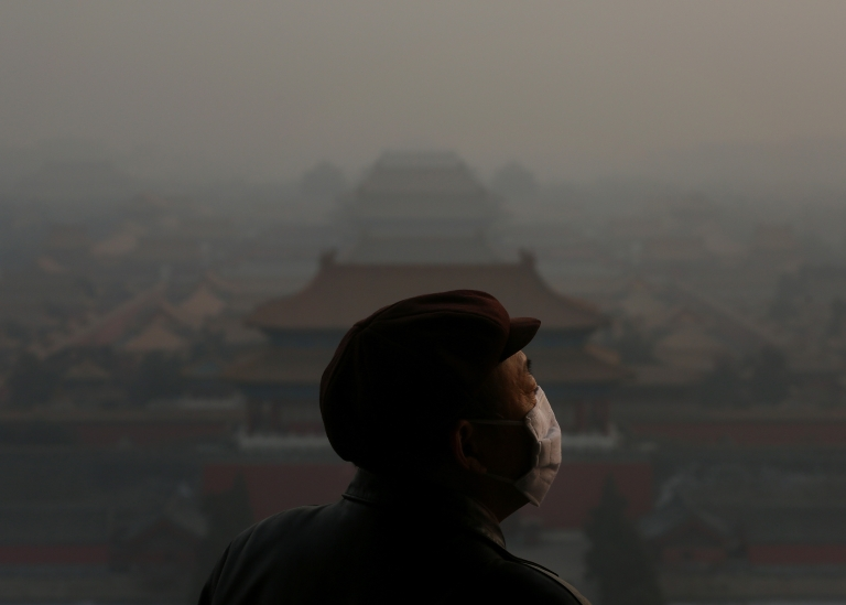<p>A tourist wearing the mask looks at the Forbidden City as pollution covers the city on Jan. 16, 2013 in Beijing, China.</p>