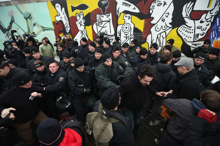 <p>BERLIN, GERMANY - Protesters scuffle with police at the East Side Gallery, which is the longest still-standing portion of the former Berlin Wall, following efforts by a construction company to remove a 25-meter long section of the Wall on March 1, 2013 in Berlin, Germany. A real estate developer is planning to build a 14-storey apartment building between the East Side Gallery and the Spree River, and needs to remove the Wall section in order to allow access to the construction site.</p>
