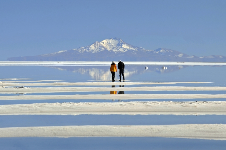 <p>A Japanese tourist couple walks on Bolivia's Uyuni, the world's largest salt flat said to also have one of the richest deposits of lithium.</p>