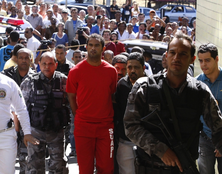 <p>Brazilian footballer Bruno Fernandes de Souza (in red) is taken into custody to the presidium of Belo Horizonte, Brazil, on July 9, 2010. De Sousa, a star goalkeeper for the popular Brazilian club Flamengo, surrendered to police Wednesday to face questioning in connection with the disappearance of his ex-girlfriend.</p>