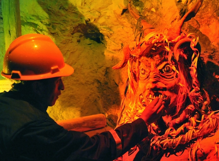 <p>A miner places a cigarette in the mouth of a statue of
