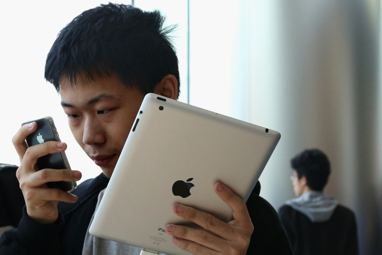 <p>In Beijing's Wangfujing Apple Store, a Chinese customer looks at an iPhone 4S in one hand, with an iPad in other.</p>