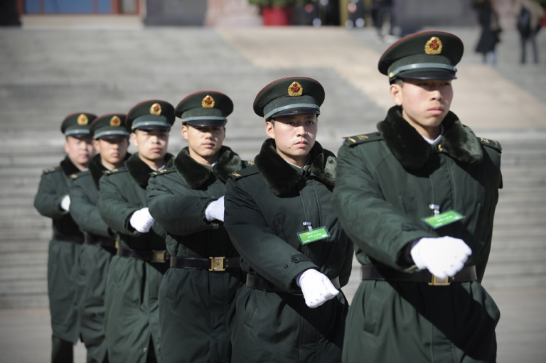 <p>A group of soldiers make their way in front of the Great Hall of the People in Beijing on March 4, 2013.</p>