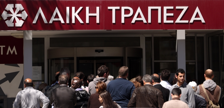 <p>Cypriots line up outside a Laiki bank branch in Cyprus' capital, Nicosia, on March 28, when banks opened after a 12-day lockdown.</p>