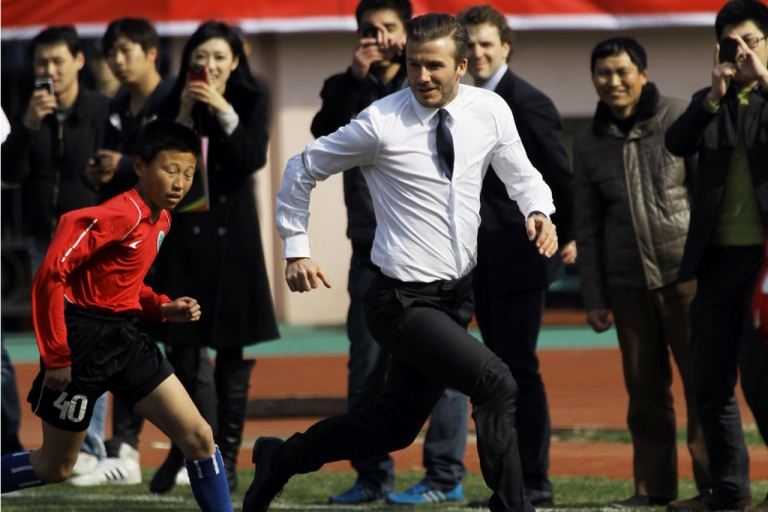 <p>David Beckham plays with a group of Chinese youngsters during a promotional event in Tiantai Stadium in Qingdao, Shandong province, on March 22, 2013.</p>