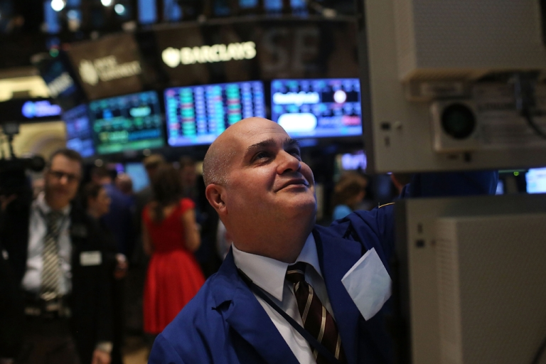<p>A trader smiles while working on the floor of the New York Stock Exchange. The Dow Jones industrial hit an all-time high on March 5, 2013, surpassing levels last seen in 2007.</p>