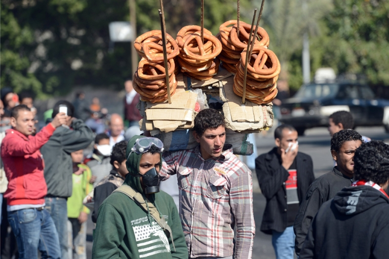 <p>An Egyptian street vender sales sweet bread as he watches nearby street clashes between riot police and protesters near Cairo's Tahrir Square, on January 29, 2013.</p>