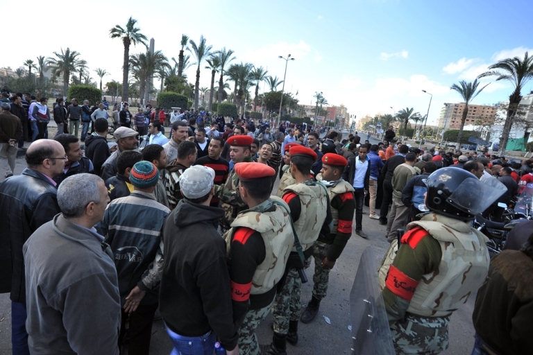 <p>Egyptian military police men speak to protestors in the Egyptian city of Port Said on March 6, 2013 following clashes between police and protesters. Police and protesters lobbed rocks at each other under a volley of tear gas that caused several people to collapse.</p>