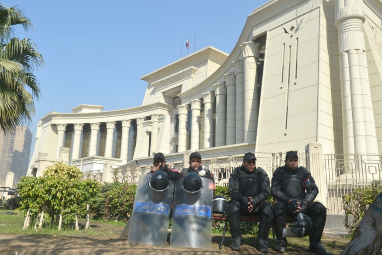 <p>Egyptian riot police sit outside the high constitutional court in Cairo on February 3, 2013.</p>