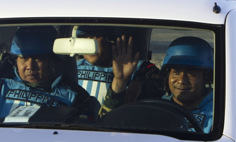 <p>Filipino UN peacekeepers cross the Quneitra checkpoint between Israel and Syria in the Golan Heights on Saturday.</p>
