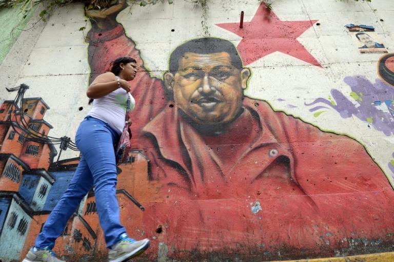 <p>A woman walks past a mural of Venezuelan President Hugo Chavez in Caracas.</p>