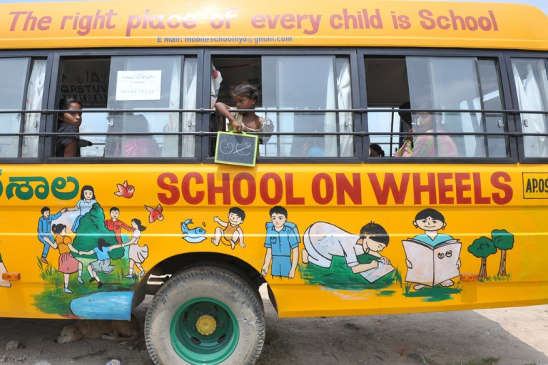 <p>Indian children study inside a bus converted to a school called the