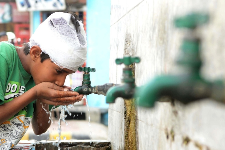 <p>An Indian boy drinks water from a tap on the roadside in Amritsar on March 22, 2013, World Water Day. Eighty percent of sewage in India is untreated and flows directly into the nation's rivers, polluting the main sources of drinking water.</p>