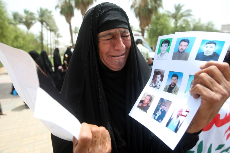 <p>An Iraqi woman cries as she holds pictures of prisoners during a demonstration at Baghdad's Tahrir Square on July 1, 2011. Protesters called for the pardon or retrial of these prisoners, saying they were sentenced after confessing to their charges under torture.</p>