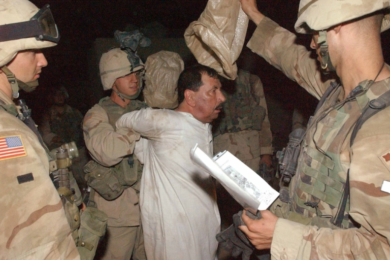 <p>In this photo from July, 2003, American forces escort a detained Iraqi to a detention center at Forward Operation Base (FOB) in Balad, 76 km north of Baghdad, Iraq. Since the beginning of the war ten years ago, human rights abuses by US, coalition and Iraqi forces against the people have not stopped.</p>