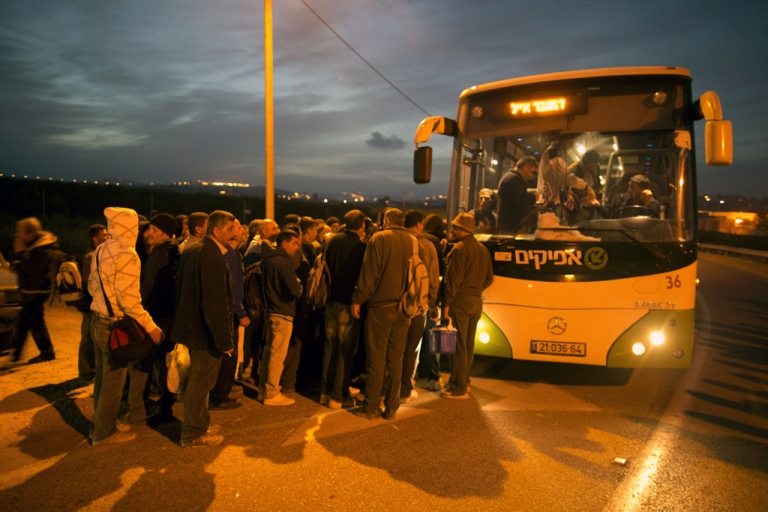 <p>Palestinians queue to board a bus as a new line is made available by Israel to take Palestinian laborers from the Israeli army crossing Eyal, near the West Bank town of Qalqilya, into the Israeli city Tel Aviv, on March 4, 2013. Thousands of Palestinians enter Israel to work every day after receiving permits, many of them in private vans. The new line will not be available for Jewish settlers.</p>