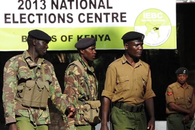 <p>Kenyan Police officers stand guard at the entrance of a polling station where Independent Electoral and Boundaries Commission (IEBC) officers work on March 7, 2013 in Nairobi. Kenya's presidential election was plunged into further disarray today after the party of one of the leading candidates alleged vote-rigging and demanded that the count be halted.</p>