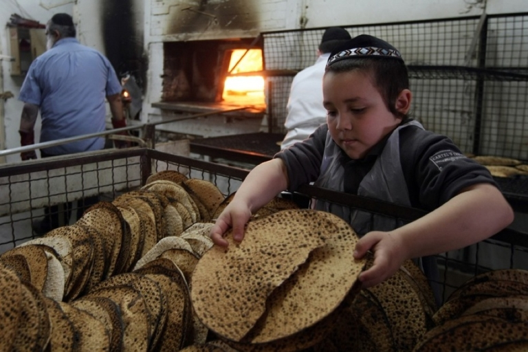 <p>An Orthodox Jewish boy inspects a Matzah, the unleavened bread eaten during Passover.</p>