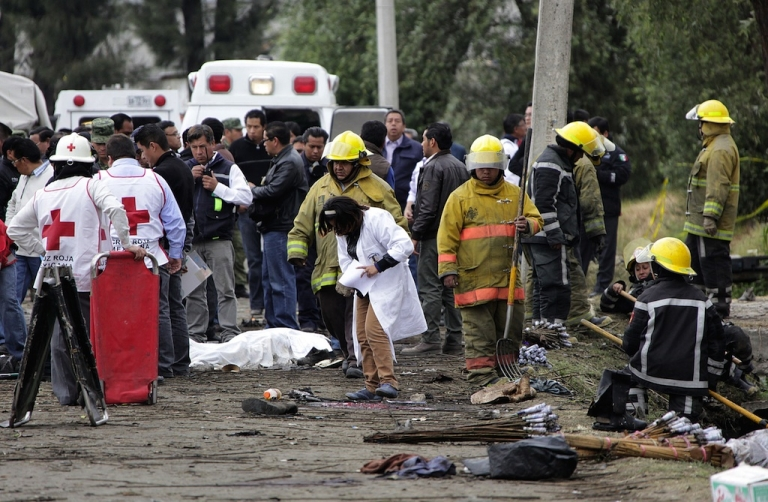 <p>Emergency rescue workers stand near one of the victims of Friday's deadly fireworks explosion in central Mexico.</p>