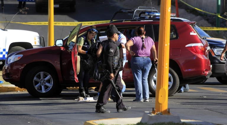 <p>Police and forensic officers at the spot where Jose de Jesus Gallegos Alvarez, the recently appointed tourism minister of Jalisco state, was shot dead on Saturday.</p>