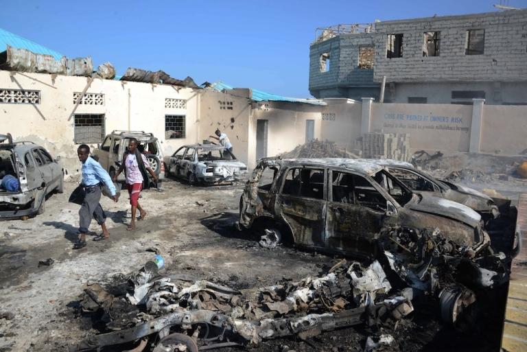 <p>People walk past the scene of a car bomb explosion close to Mogadishu's famous Lido beach on Feb. 16, 2013.</p>
