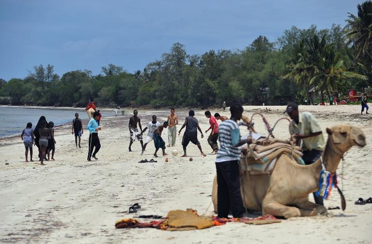 <p>A man prepares his camel for tourists as boys play soccer at the Kenyatta public beach on the Kenyan coast.</p>
